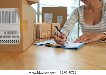 Woman writing down addresses for the parcels she is going to send