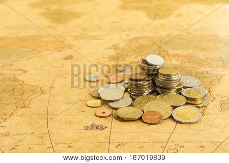 Heap of money gold coins on old world map currency and economy concepts.