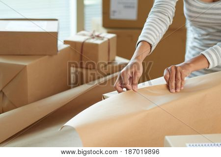 Cropped image of woman wrapping presents with craft paper