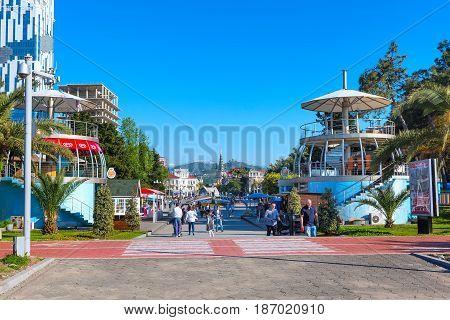 Batumi, Georgia - April 30, 2017: People walking in the park with palm trees near promenade boulevard of georgian summer resort