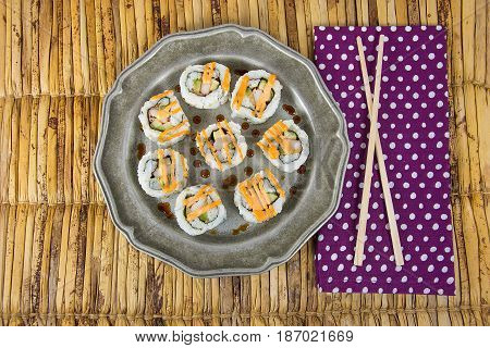 sushi on pewter plate with chopstick on polka dot napkin and bamboo place mat