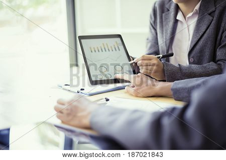 Business people analyzing investment charts with teblet in meeting room Accounting concept soft focus vintage tone