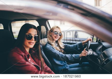 Smiling Happy Young Woman Giving Her Friend A Lift In Her Car In Town, Profile View Through The Open