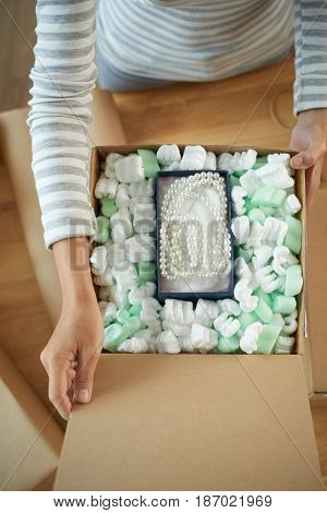 Hands of woman opening parcel with jewelry inside, view from above