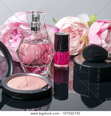 Perfume bottle, makeup brush, nail polish and blusher. Fashion woman still life. Pop female things on black background with flowers. Beauty tools.