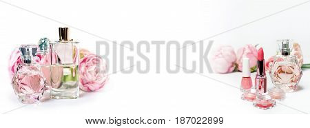 Perfume bottles with flowers on light background. Perfumery, cosmetics, fragrance collection. Free space for text. Banner for website