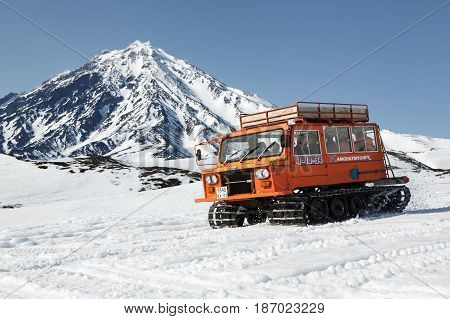 KORYAKSKY VOLCANO KAMCHATKA PENINSULA RUSSIA - APR 26 2014: Snowcat transportation sportsman (skiers and snowboarders) on snowy slopes of mountains on background of beautiful stratovolcano.