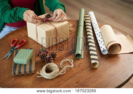 Creative woman using craft paper, berries and cones when wrapping present