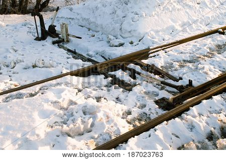 Railway junction and switch on winter railroad.