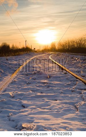 Railroad in the sunset rays in winter.