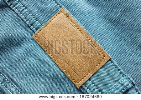 Blank leather clothes label on blue denim closeup as a background
