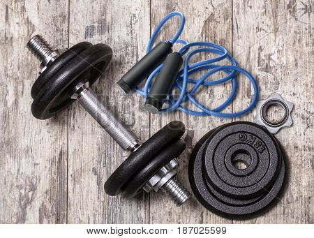 Athlete's set with dumbbells and skipping rope on wooden background