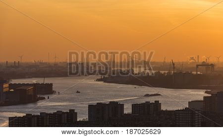 Nieuwe Maas in Evening Light with ships on the river industrial areas and the harbor of Rotterdam in the Netherlands.