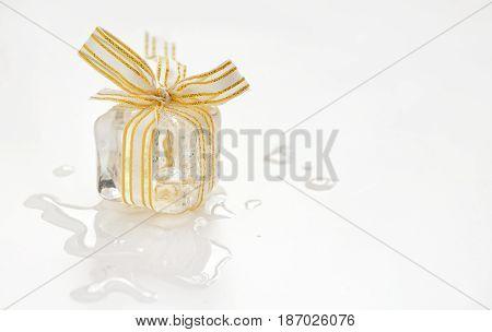 Melting ice cube gift, close up on white background