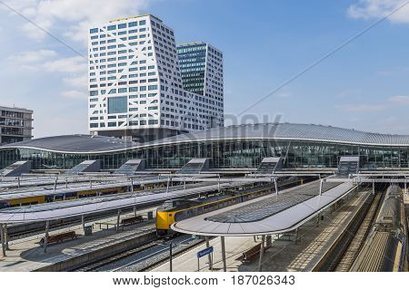 Utrecht The Netherlands - March 23 2017: Railway station Utrecht Centraal of the NS with glass roofs platforms and office buildings (Stadskantoor).