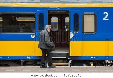 Rotterdam The Netherlands - March 10 2017: Old man at the platform near the door of a train in railway station of Rotterdam in the Netherlands.