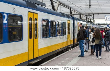 Rotterdam The Netherlands - March 10 2017: Travelers at the platform near the door of a train in railway station Rotterdam in the Netherlands.