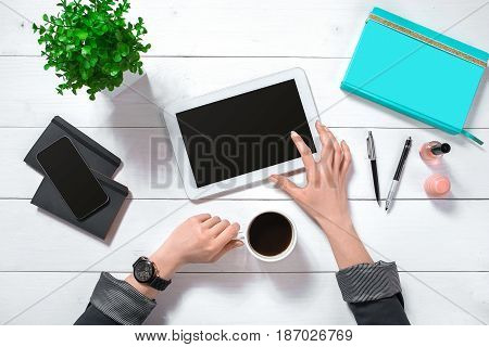 Close up of woman's hands with long fingers holding tablet. Smartphone and notebook lie on table. Top view. Copy space