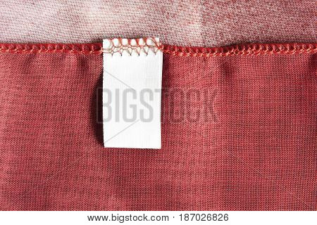 Blank white clothes label on red silk closeup