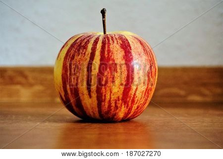 Photo of a single apple on a wooden table