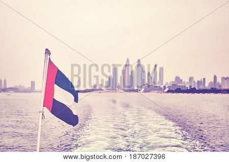 Vintage stylized United Arab Emirates flag with Dubai skyline in distance selective focus.