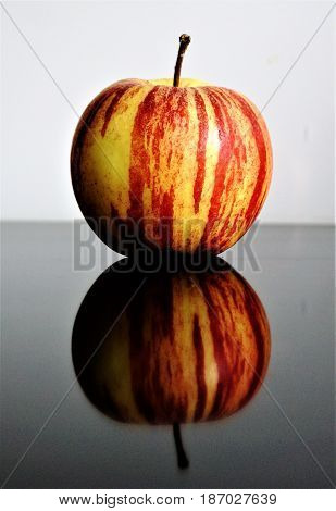 Photo of an apple reflecting on a glass table
