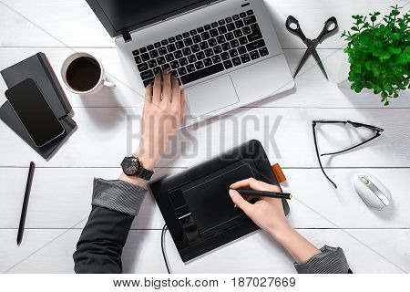 Top view of woman's hands typing on laptop keypad placed on white office desktop with coffee cup. Mock up