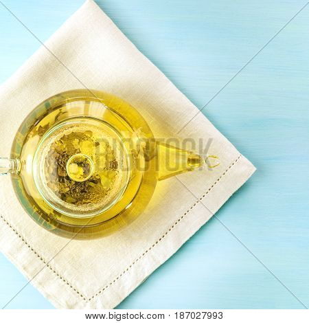 An overhead photo of a teapot with a tea flower in it, with a place for text, toned image, square photo