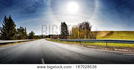 asphalt road panorama in countryside on sunny spring evening