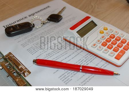 Insurance policy and key from the car. Insurance concept. Car insurance form with car keys pen and calculator on the table