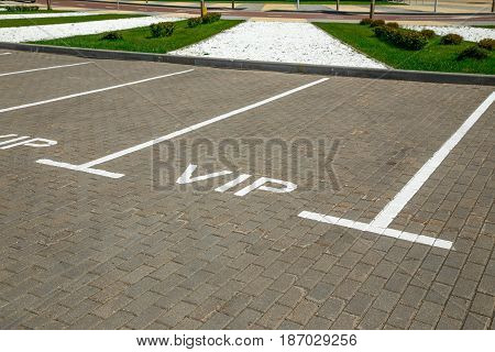 Empty parking space separated by white stripes markings. The parking place has an inscription VIP