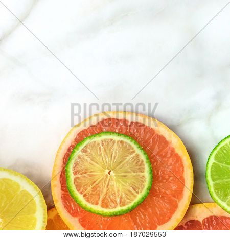 Vibrant juicy citrus fruits on a white marble texture with copy space. Grapefruit, lime, lemon, and orange slices, square photo