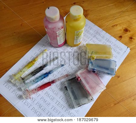 Set of Ink cartridges, refill paint in bottles and dirty syringes. On printed test page. Jet printer maintenance. Selected focus.