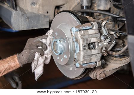Assembler cleans a brake disc after installation in the car repair