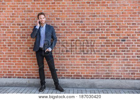 Man talking business on phone holding smartphone in city street in smart casual wear standing against brick wall urban background. Happy caucasian businessman.