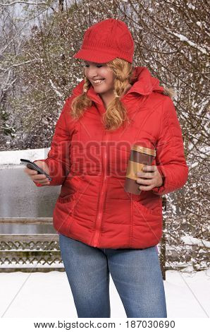 Woman using a cell phone and holding a disposable to go coffee cup