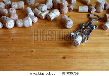 Wooden table with lot of wine and champagne corks. Corkscrew at the right. Alcohol concept background. Rural or retro style. With place for text.