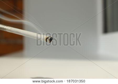 A Glowing , smoldering, smoking , Burning cigarette