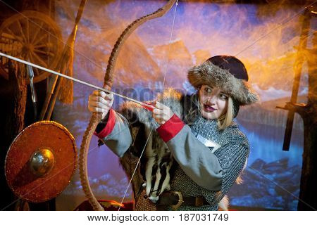 A woman with blond hair in the costume of a warrior of the times of Kiev Rus in chain mail with a bow and arrow aiming