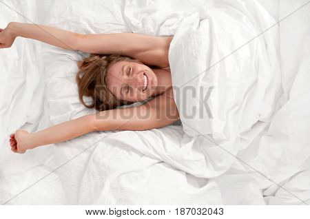 Woman Waking Up And Yawning After Sleep On Bed
