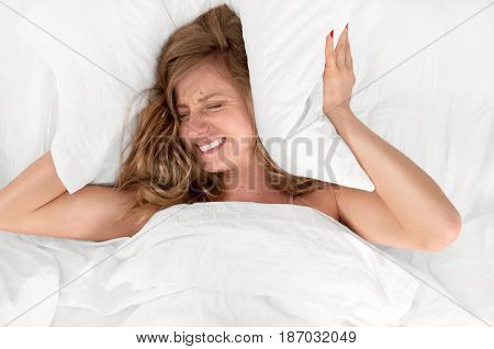 Too much noise. Woman in bed covering ears with pillow because of noise.