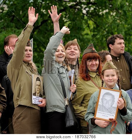 Orel Russia - May 9 2017: Victory Day selebration. Smiling people in Soviet war uniform waving hands in Immortal Regiment square