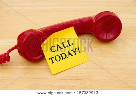 Call Today for assistance Retro red phone handset with a yellow sticky note and text Call Today