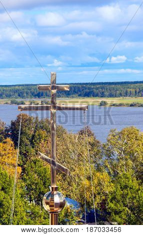Orthodox golden cross over the river. Sunny autumn day. Volga river Russia