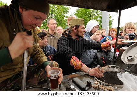 Orel Russia - May 9 2017: Victory Day selebration. People in war uniform giving out tea and buckwheat porridge from field kitchen closeup