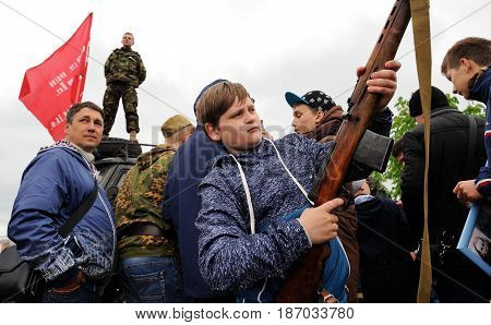 Orel Russia - May 9 2017: Victory Day selebration. Boy in crowd checking rifle horizontal