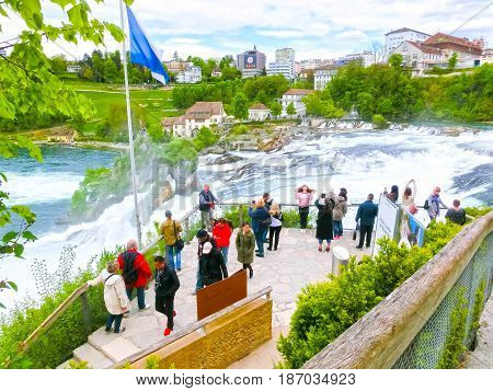 Schaffhausen, Switzerland - May 01, 2017: The people making photos near the largest waterfall in Europe by River Rhein in Schaffhausen, Switzerland on May 01, 201
