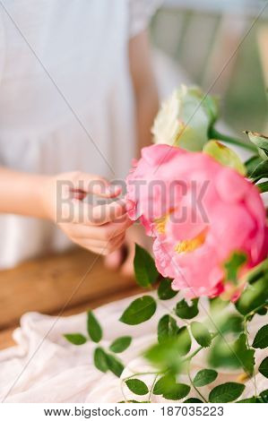 wedding, childcare, floral design, celebration, decoration concept - little soft hand of girl in white dress touching grand blooming bud of peony sorrounded by green leaves