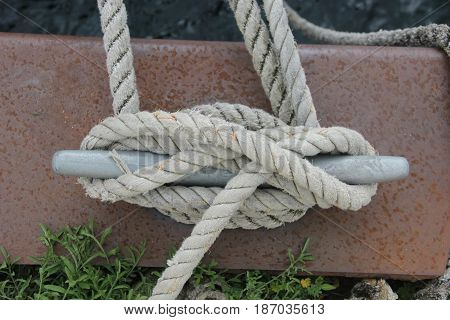 A rope tied around a cleat on shore