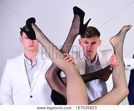 men or businessmen in jacket and female sexy legs in fashionable shoes and tights on grey background love and relations power boss office romance sexual services